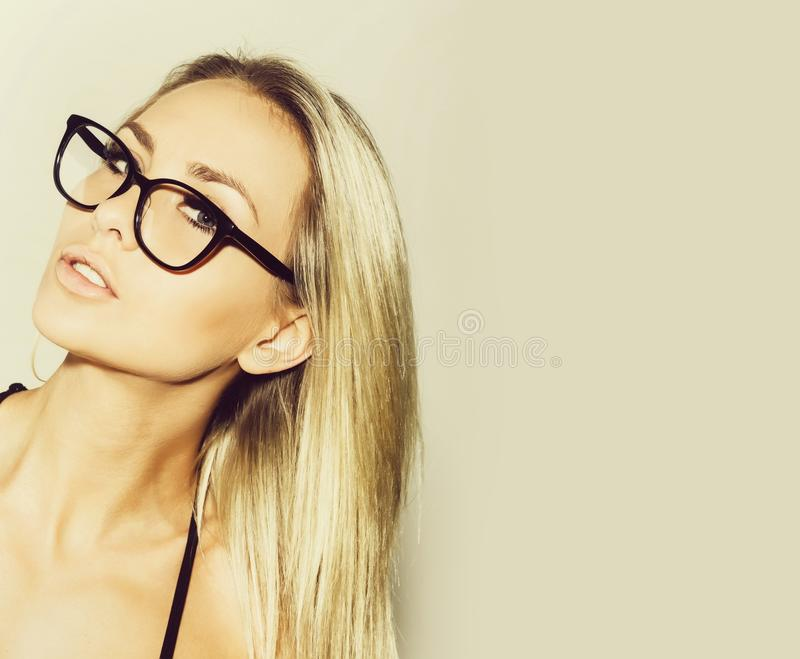 Pretty student girl or blonde teacher woman in black eyeglasses stock photography