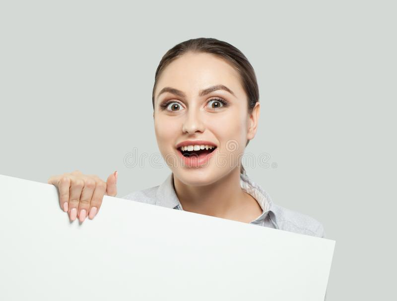 Pretty student girl having fun and holding white empty signboard background with copy space. Young businesswoman smiling stock image