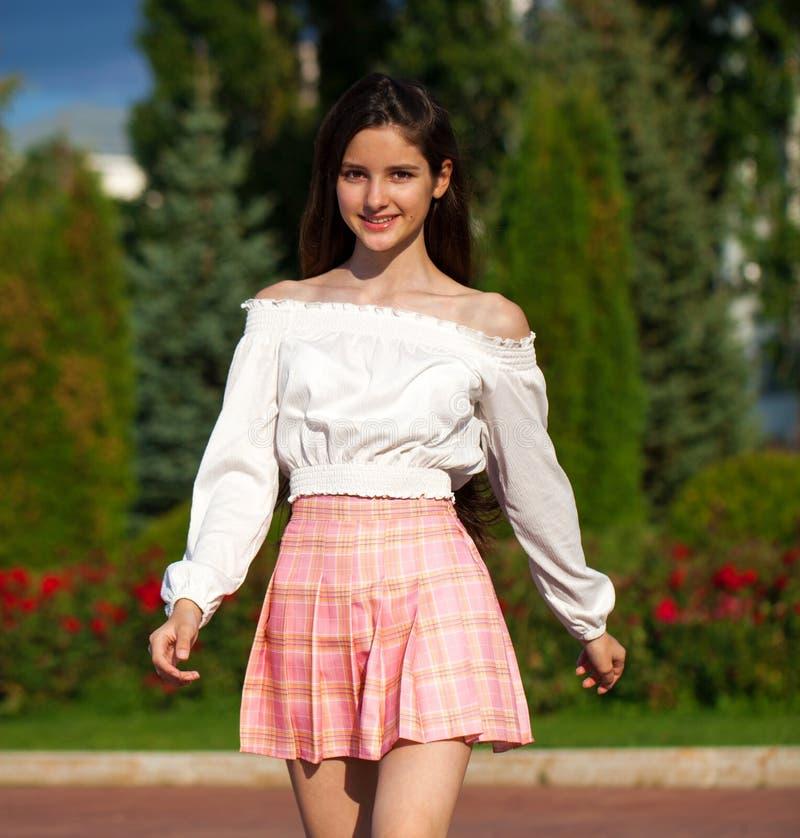 Pretty stylish brunette girl in plaid skirt and white blouse. Pretty stylish brunette girl in pink plaid skirt and white blouse posing in summer park background royalty free stock image