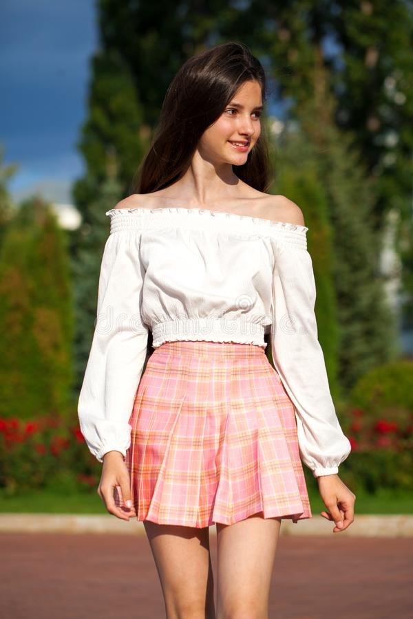 Pretty stylish brunette girl in plaid skirt and white blouse. Pretty stylish brunette girl in pink plaid skirt and white blouse posing in summer park background stock photography