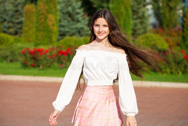 Pretty stylish brunette girl in plaid skirt and white blouse. Pretty stylish brunette girl in pink plaid skirt and white blouse posing in summer park background royalty free stock photo