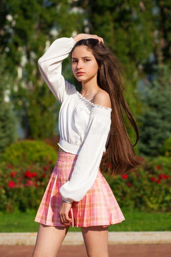 Pretty stylish brunette girl in plaid skirt and white blouse. Pretty stylish brunette girl in pink plaid skirt and white blouse posing in summer park background stock image
