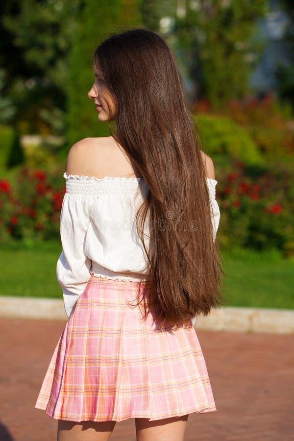 Pretty stylish brunette girl in plaid skirt and white blouse. Pretty stylish brunette girl in pink plaid skirt and white blouse posing in summer park background stock images
