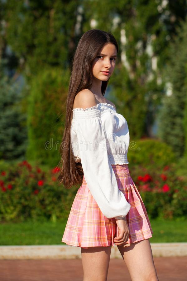 Pretty stylish brunette girl in plaid skirt and white blouse. Pretty stylish brunette girl in pink plaid skirt and white blouse posing in summer park background royalty free stock photography