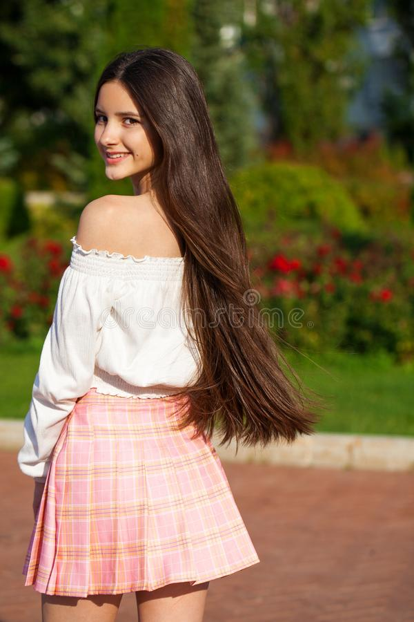 Pretty stylish brunette girl in plaid skirt and white blouse. Pretty stylish brunette girl in pink plaid skirt and white blouse posing in summer park background royalty free stock images
