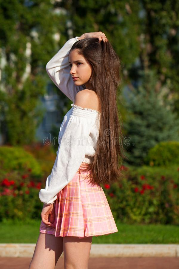 Pretty stylish brunette girl in plaid skirt and white blouse. Pretty stylish brunette girl in pink plaid skirt and white blouse posing in summer park background stock photos