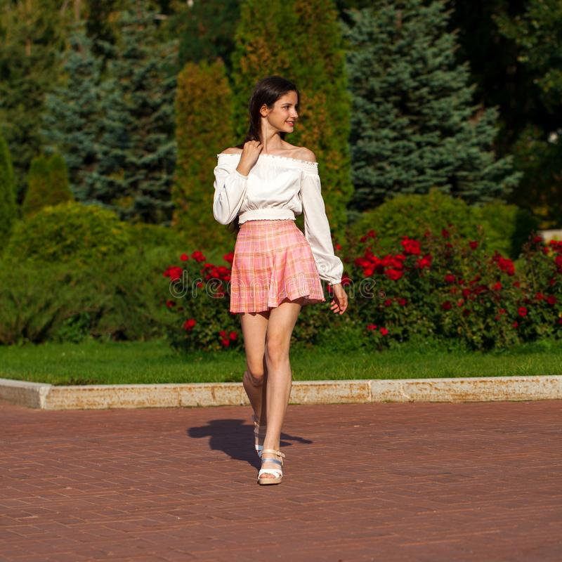 Pretty stylish brunette girl in plaid skirt and white blouse. Posing in summer park background royalty free stock photos