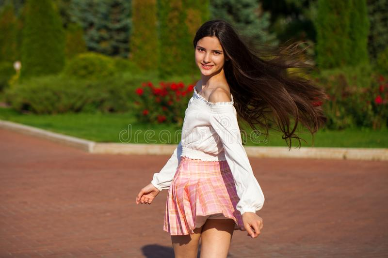 Pretty stylish brunette girl in plaid skirt and white blouse. Posing in summer park background royalty free stock photography