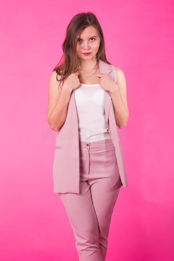 Pretty stylish girl with long hair posing against pink background. Fashion portrait of young happy smiling woman.  stock photography