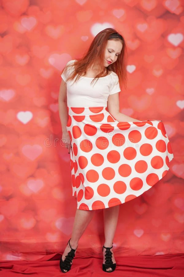 Pretty stylish pin up girl in white shirt and red polka dot vintage skirt standing on red hearts background. Alone stock photos