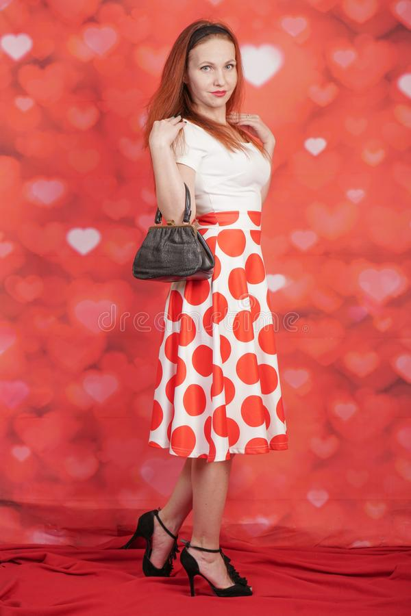 Pretty stylish pin up girl in white shirt and red polka dot vintage skirt standing on red hearts background. Alone royalty free stock photos