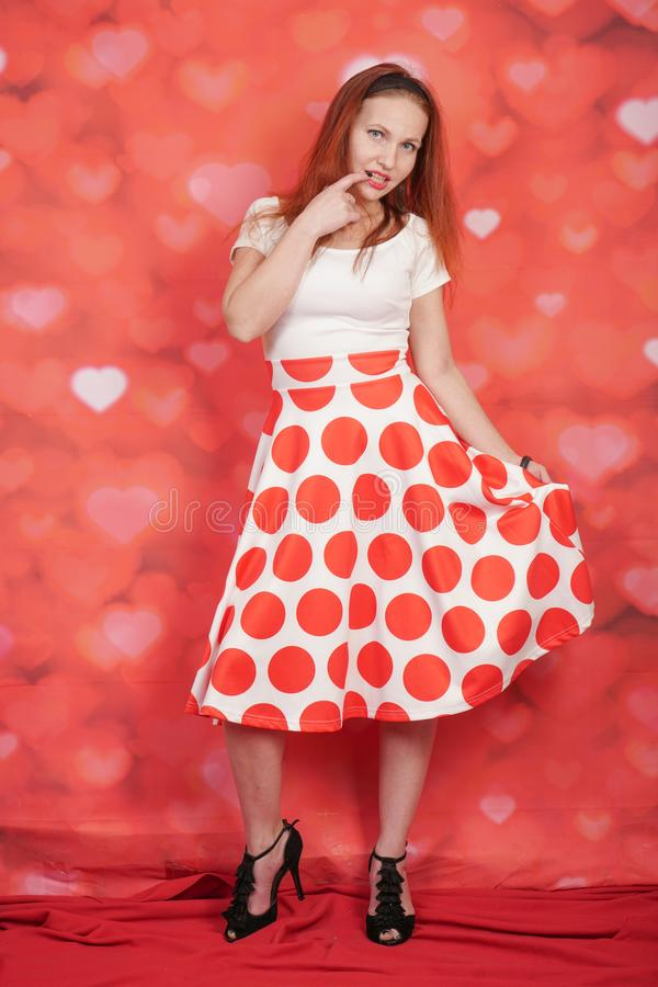 Pretty stylish pin up girl in white shirt and red polka dot vintage skirt standing on red hearts background. Alone royalty free stock photo