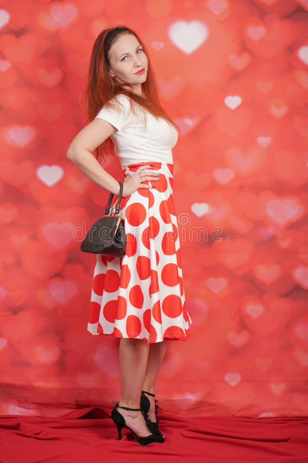 Pretty stylish pin up girl in white shirt and red polka dot vintage skirt standing on red hearts background. Alone stock images