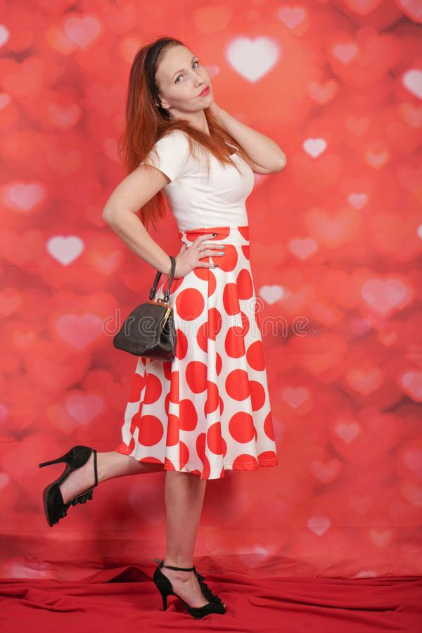 Pretty stylish pin up girl in white shirt and red polka dot vintage skirt standing on red hearts background. Alone royalty free stock photography