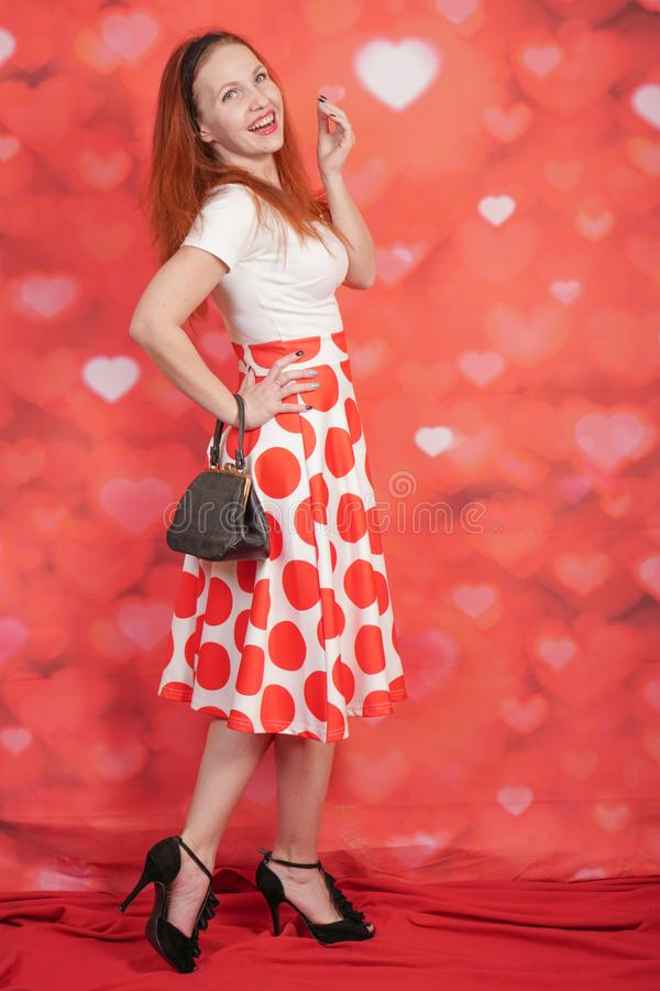Pretty stylish pin up girl in white shirt and red polka dot vintage skirt standing on red hearts background. Alone royalty free stock images