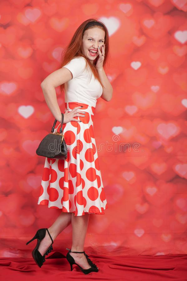 Pretty stylish pin up girl in white shirt and red polka dot vintage skirt standing on red hearts background. Alone stock photo