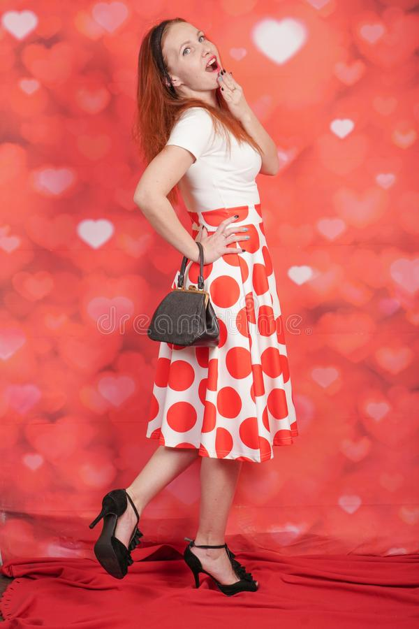 Pretty stylish pin up girl in white shirt and red polka dot vintage skirt standing on red hearts background. Alone stock image