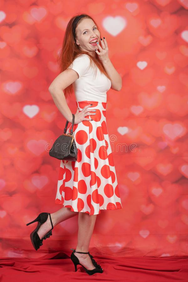 Pretty stylish pin up girl in white shirt and red polka dot vintage skirt standing on red hearts background. Alone stock photography