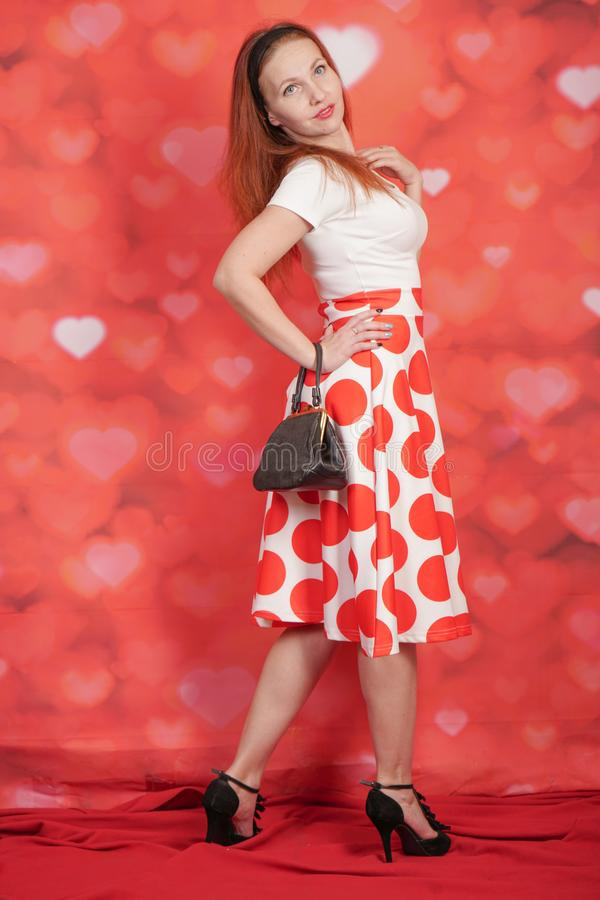 Pretty stylish pin up girl in white shirt and red polka dot vintage skirt standing on red hearts background. Alone royalty free stock image