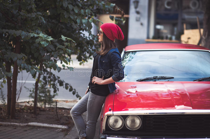 Pretty stylish woman standing by the retro car stock image