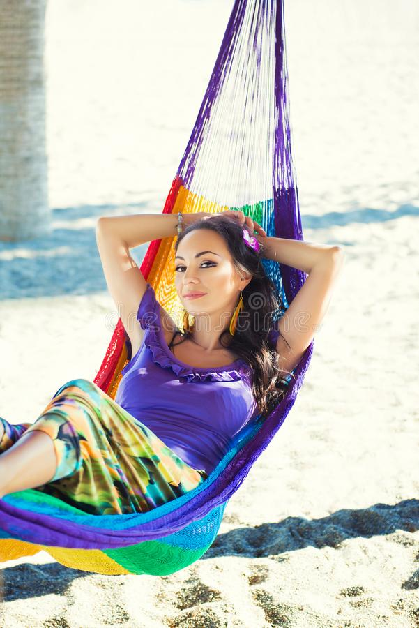 Pretty surprised cheerful young girl on the beach, smiling lies in a hammock against the backdrop of palm trees, lifestyle, tanned stock photos