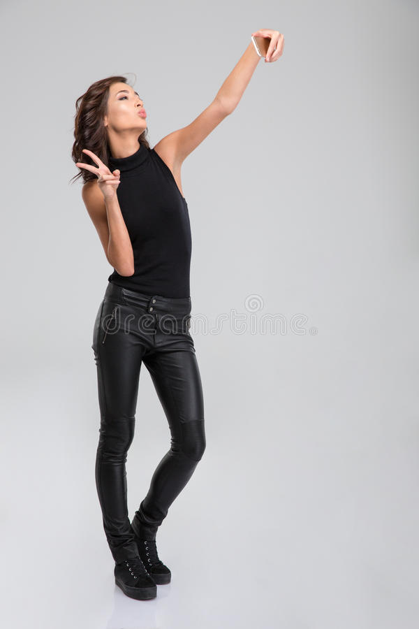 Pretty sweet young female taking self portrait with smart phone. Pretty sweet curly young female in black leather pants and top taking a self portrait with smart royalty free stock images
