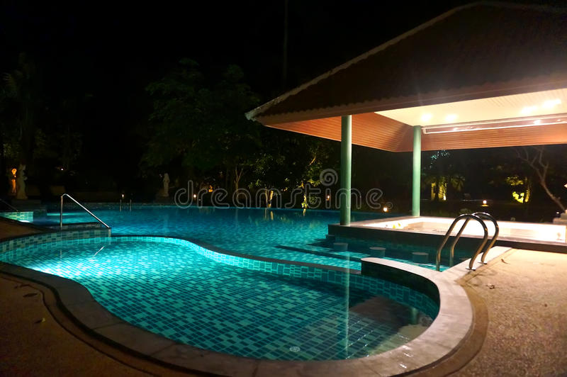 A pretty swimming pool in night at a local resort royalty free stock photography