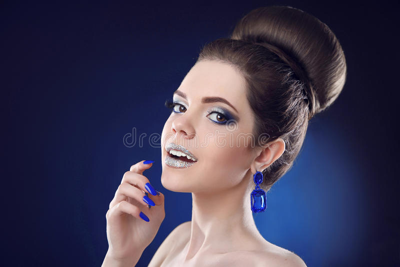 Pretty teen girl with cute bun hairstyles, beauty fashion glitter makeup and blue manicured nails, gems earring jewelry posing on stock photography