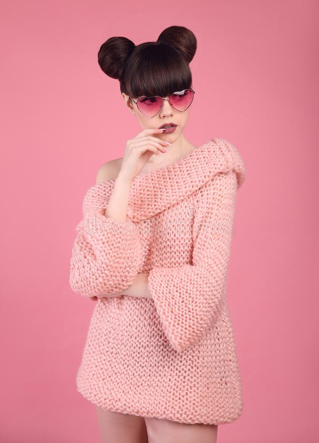 Pretty teen girl in knitted sweater over pink background. Fashion photo teen look style. Brunette with bun hairstyle posing on st royalty free stock photo