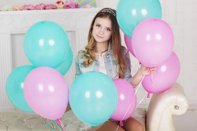 Pretty teen girl with many blue and pink balloons stock image
