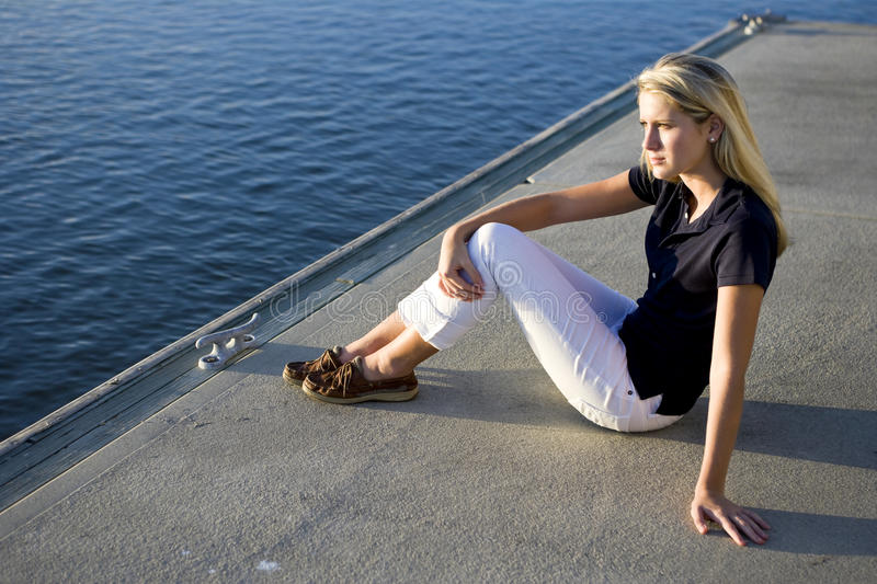 Pretty teen girl sitting on dock by water watching royalty free stock photography