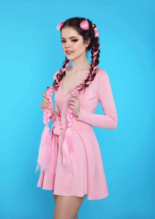 Pretty teen girl with two french braids from pink kanekalon, fashionable hairdo for youth, creative hairdresser beauty salon. Positive brunette posing in cute royalty free stock image