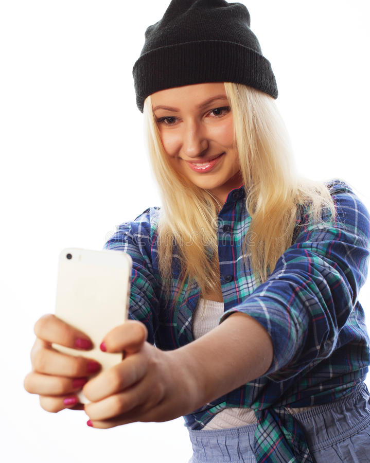 Pretty teen girl wearing hat, taking selfies. People, lifestyle and tehnology concept: pretty teen girl wearing hat, taking selfies with her smart phone stock photo