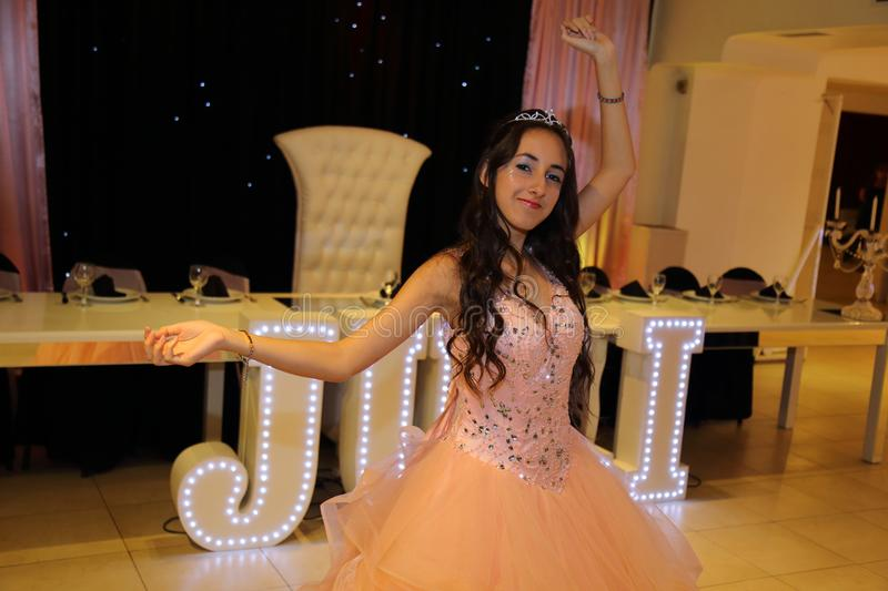 Pretty teen quinceanera birthday girl celebrating in princess dress pink party, special celebration of girl becoming woman. royalty free stock photos