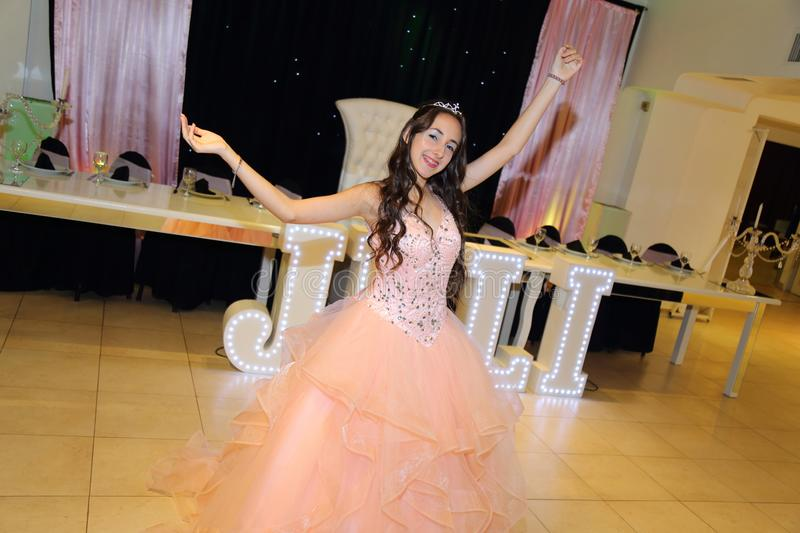 Pretty teen quinceanera birthday girl celebrating in princess dress pink party, special celebration of girl becoming woman. stock photo