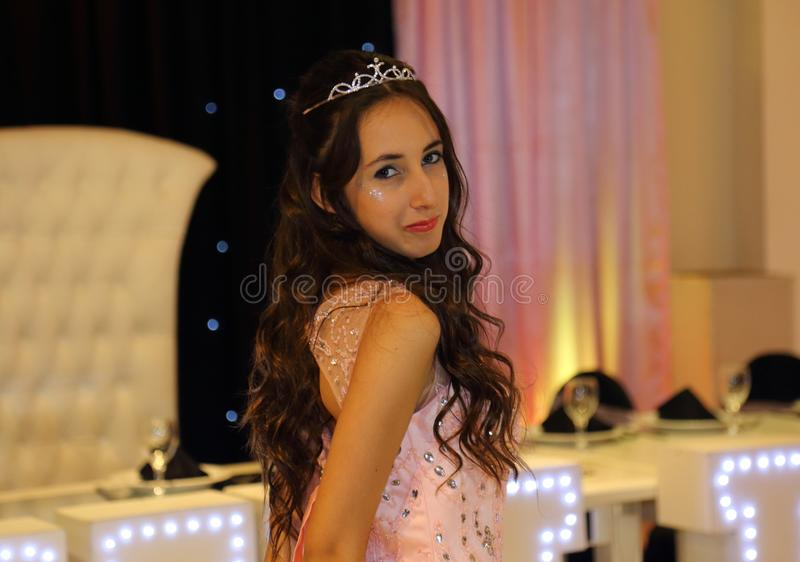 Pretty teen quinceanera birthday girl celebrating in princess dress pink party, special celebration of girl becoming woman. royalty free stock image