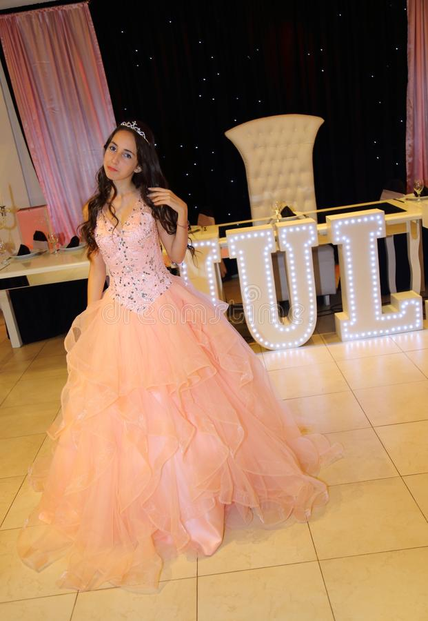 Pretty teen quinceanera birthday girl celebrating in princess dress pink party, special celebration of girl becoming woman. Love and family celebration an stock images