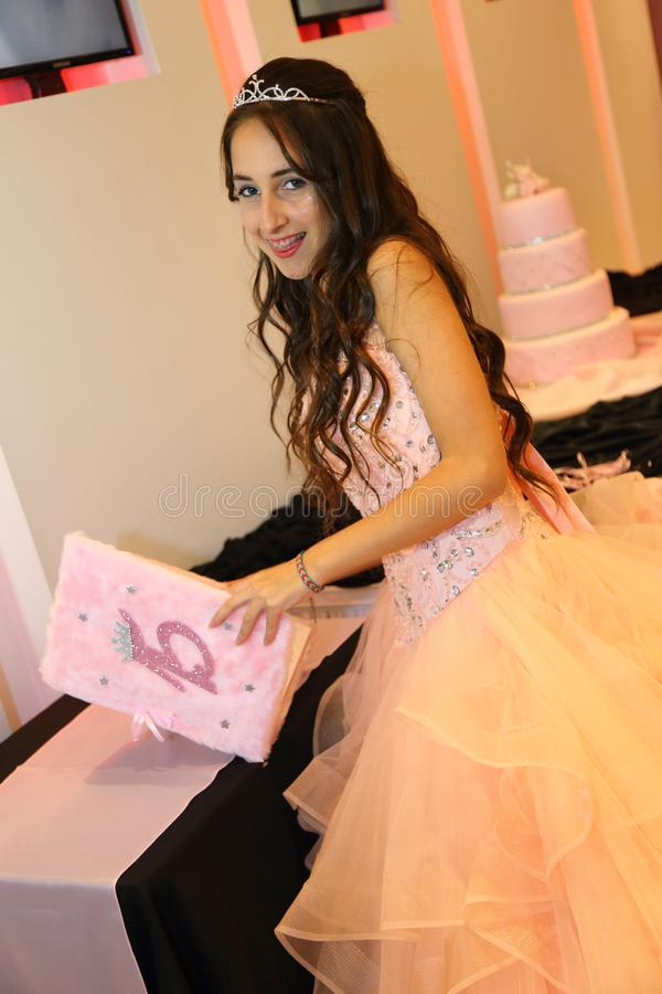 Pretty teen quinceanera birthday girl celebrating in princess dress pink party, special celebration of girl becoming woman. Love and family celebration an royalty free stock image