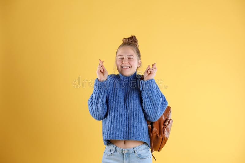 Pretty teenage girl with backpack crossing her fingers stock photo