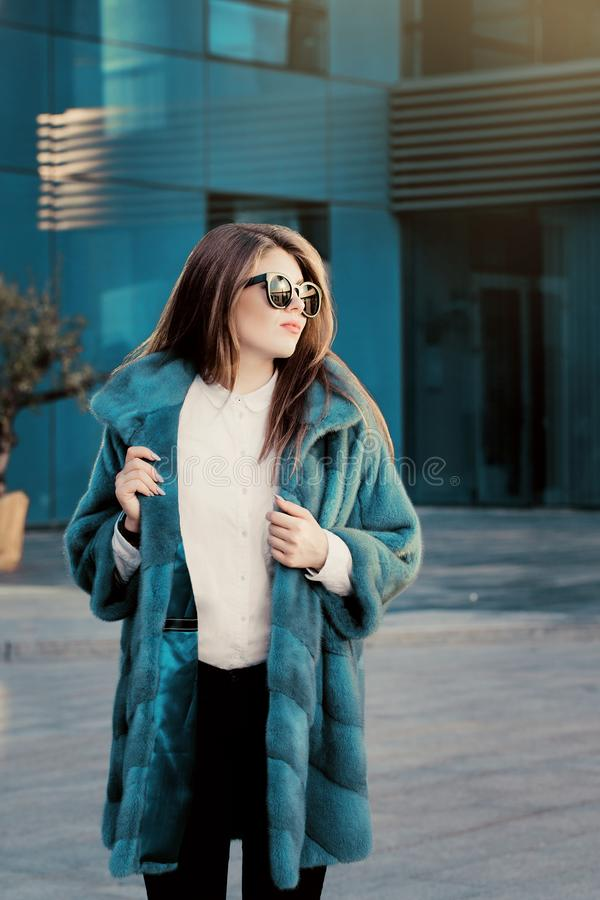 Pretty teenage girl in a bright colorful natural fur coat and sunglasses stock images