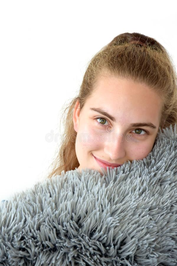 Pretty teenage girl cuddling with pillow royalty free stock images