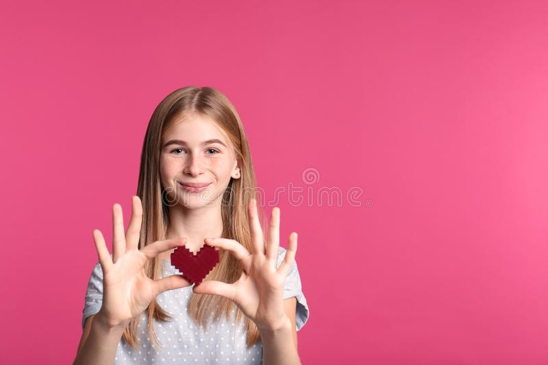 Pretty teenage girl with decorative heart on color background. stock image