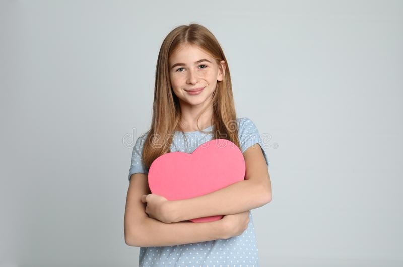 Pretty teenage girl with decorative heart on color background. royalty free stock images