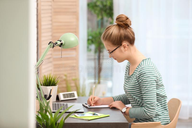 Pretty teenage girl doing homework at table stock image