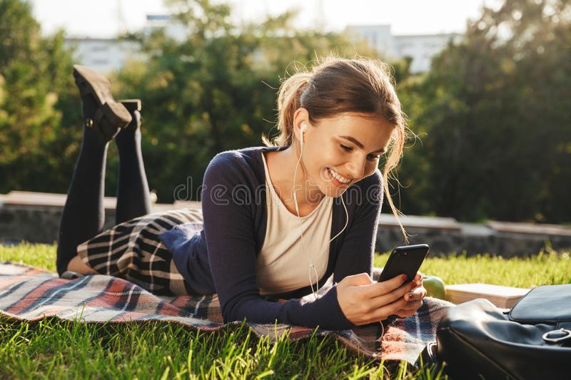 Pretty teenage girl laying on a grass at the park stock photos