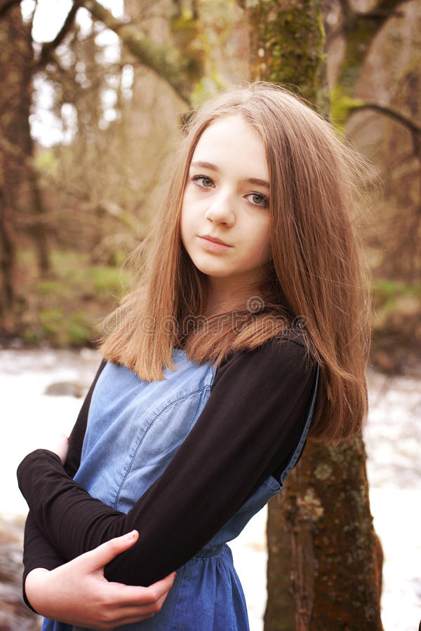 Pretty teenage girl leaning against a tree stock images