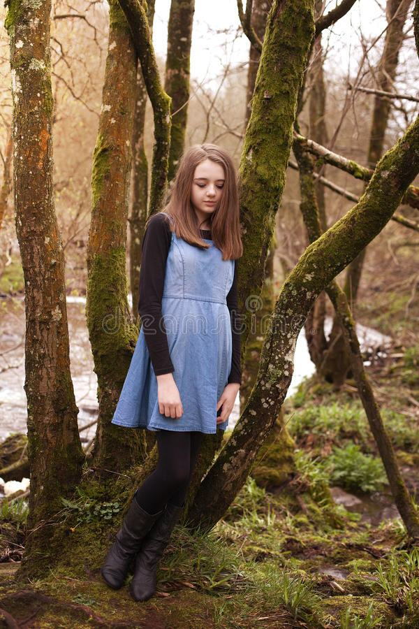 Pretty teenage girl leaning against a tree stock photo