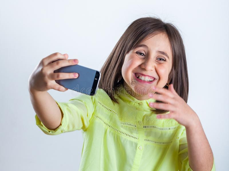 Pretty teenage girl with mobile phone in studio. Selfie royalty free stock images