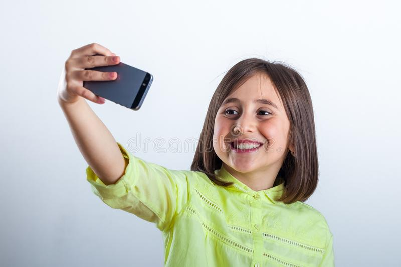 Pretty teenage girl with mobile phone in studio. Selfie stock photos