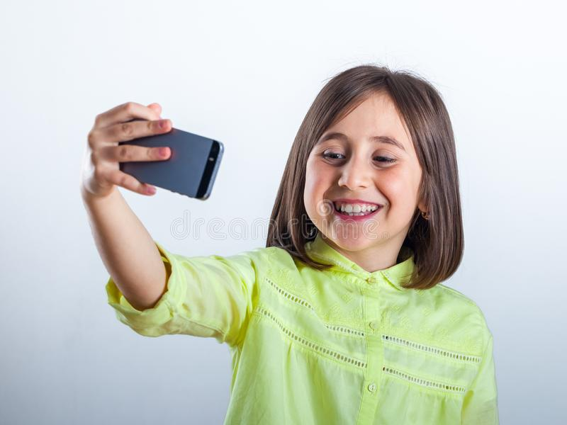Pretty teenage girl with mobile phone in studio. Selfie royalty free stock photos